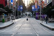 A lone photographer takes kneels to take a photo of the lockdown Bourke Street as the state waits to see if the lockdown will be extended as it enters 6th day of the state wide COVID-19 snap lockdown that has been placed on the State of Victoria.  (Photo by Michael Currie/Speed Media)