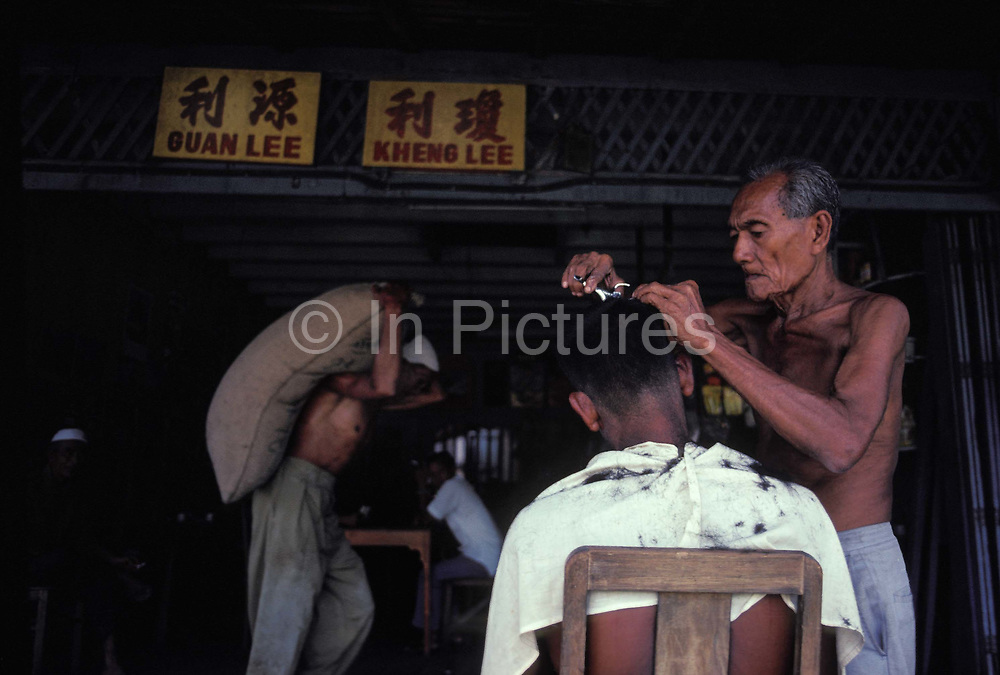 With Chinese characters of a nearby business behind, a market trader carries a heavy sack of produce while a local barber snips at the hair of a customer in a Malaysian kampung, a river village within Bako National Park, one of Southeast Asia's smallest national parks, 37km ride from Kuching on the Rajang River, on 14th March 1982, in Bako Kampung, Sarawak, Borneo, Malaysia.