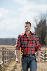 rugged man in a flannel shirt walking on a ranch