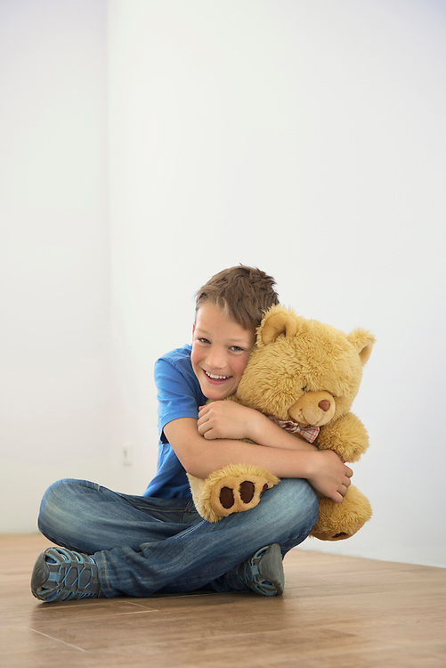 Happy young boy holding toy teddy new home