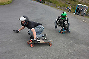 Two long boarders descend a hill on private road in Tregaron, Wales. During the downhill longboard races held on private land on a Sunday afternoon in mid-Wales, men and women of all ages try to dominate their mates and fellow-competitors in a series of heats throughout the day. The private road is steep and the racers need to angle themselves in order to negotiate the bend. Crouching low with a balancing gloved hand that scrapes the ground and wearing helmets and a Go-Pro camera on the top, the men whiz down past spectators to the bottom.