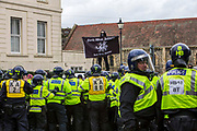 A lone Facist supporter stands high above police lines showing his Anglo Saxon flag at the Anti Facist group from behind police lines keeping two opposing groups separate as Anti Facist demonstrators march through Dover protesting against a facist demonstration also taking place in the port town. 30th January 2016