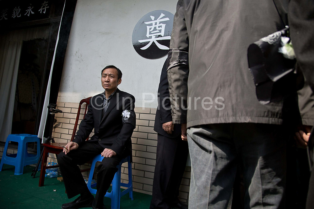 An usher sits outside of a house where the body of late village party chief Wu Renbao lays at Huaxi, Jiangsu Province, China on 22 March  2012.  Wu is a outlier among local political leaders as his village is one of the wealthiest in China while remaining a collective, building up a personality cult that is much larger than his official title reflects.