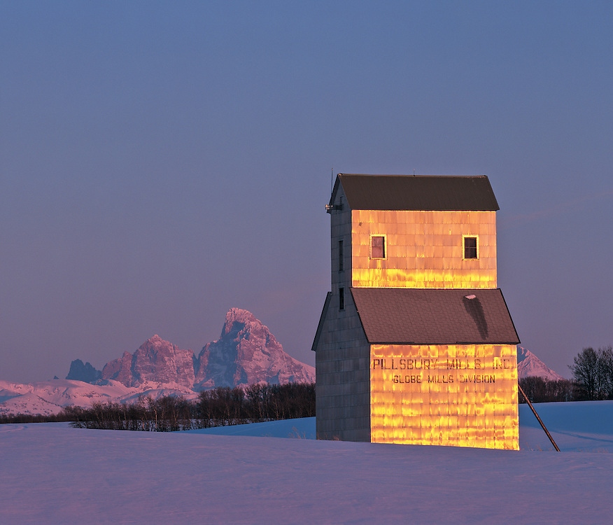 Edition of 65 includes all sizes<br /> Grain Elevator in Drummond Idaho reflects a winter sunset with the Teton Mountain Range in the distant background on the Eastern Idaho agricultural prairie