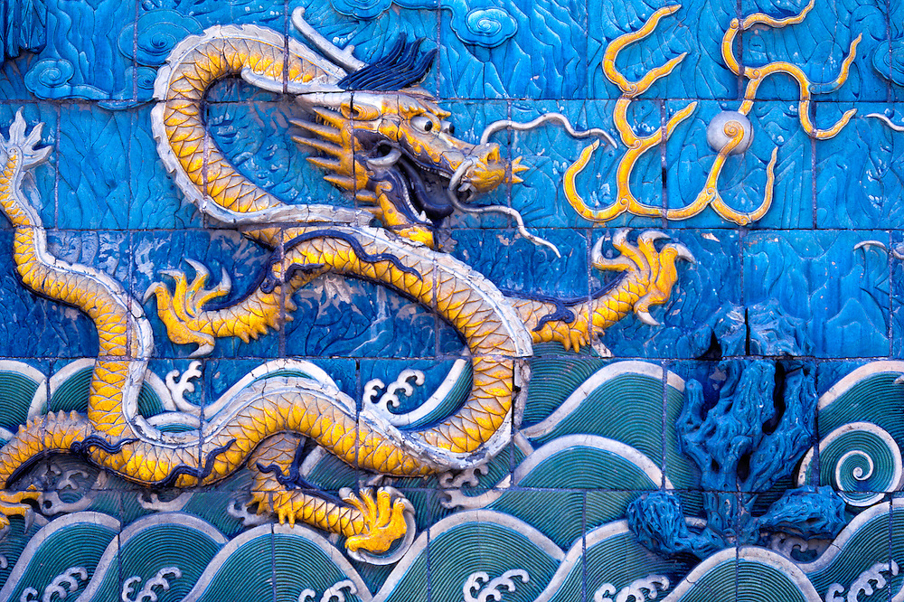 Stylized dragons nearly jump from this tiled wall, in the Forbidden City, Beijing, China.