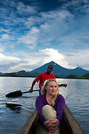 Lake Mutanda, Uganda, April 2014. Taking a sundowner cruise in a dugout canoe supports the local population with community tourism income. Mutanda Lake Resort lies on a peninsula in the shadow of the Virunga Mountain Range offering some of the most beautiful views on planet earth. Situated between Kisoro town, Mgahinga and Bwindi National Parks it makes a perfect base for gorilla trackers, volcano hikers, bird lovers as well as those looking for a secluded place in nature.  East of Lake Victoria, at the borders with Congo (DRC) and Rwanda, is where the East African savannah meets the West African jungle highlands and mountains. The route of our roadtrip becomes an epic journey over potholed mountain dirt roads, with a 4x4 vehicle, through some of Africa's most spectacular landscapes, various cultures, and National Parks. Photo by Frits Meyst / MeystPhoto.com