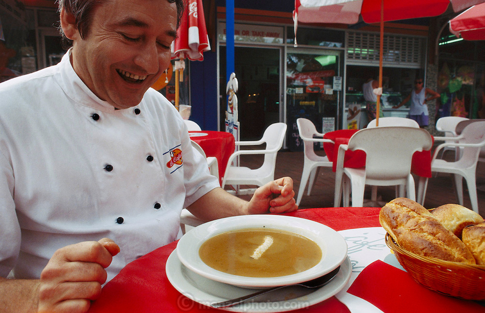 """Chef Jean-Pierre Rodot at his restaurant, La Cafeterie, with a bowl of witchetty grub soup in Alice Springs, Central Australia. A live witchetty grub (Witchetty grubs are the larvae of cossid moths) floats on top of the soup. Rodot loves witchetty grubs and ate this one alive, savoring its yellow egg-yolk-like guts and declaring them """"Delicious!"""" (pages 4,5. See also page 23)."""
