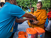 11 AUGUST 2015 - BANGKOK, THAILAND:  People make merit by presenting donations to Buddhist monks during a service to honor Queen Sirikit of Thailand before her 83rd birthday. Queen Sirikit was born Mom Rajawongse Sirikit Kitiyakara on August 12, 1932. She is the queen consort of Bhumibol Adulyadej, King (Rama IX) of Thailand. She met Bhumibol in Paris, where her father was the Thai ambassador. They married in 1950, she was appointed Queen Regent in 1956. The King and Queen had one son and three daughters. She has not made any public appearances since her hospitalization in 2012. Her birthday is celebrated as Mother's Day in Thailand, schools and temples across Thailand hold ceremonies to honor the Queen and mothers.      PHOTO BY JACK KURTZ