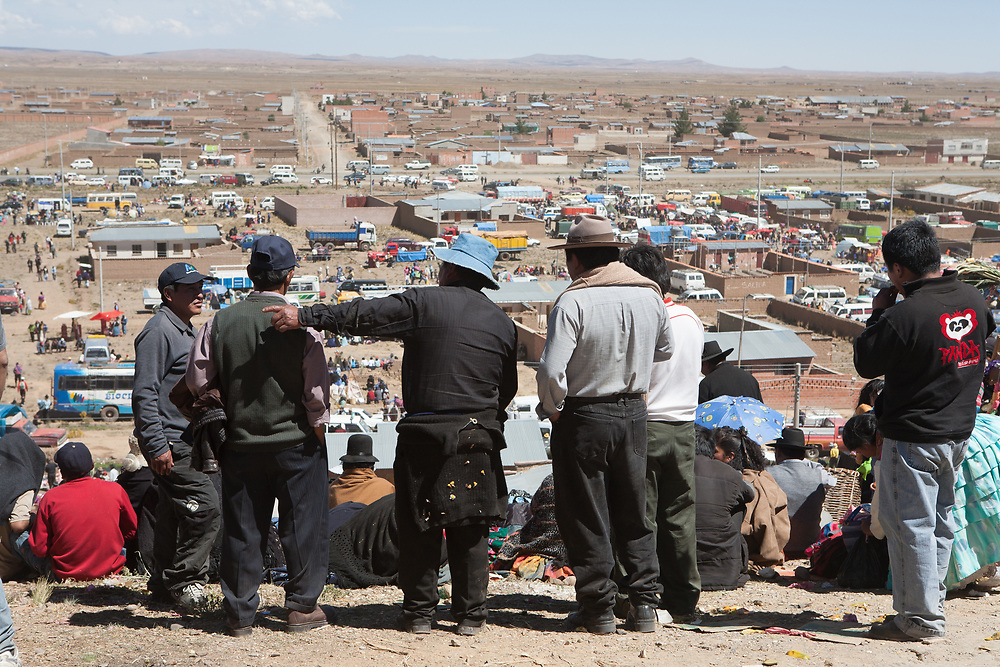 People stand on a hill overlooking a village in the altiplano of Bolivia.