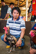 11 JANUARY 2014 - BANGKOK, THAILAND: A cock owner in a fighting pit in Bangkok. Cockfighting dates back over 3,000 years and is still popular in many countries throughout the world today, including Thailand. Cockfighting is legal in Thailand. Unlike some countries, Thai cockfighting does not use artificial spurs to increase injury and does not employ the 'fight to the death rule'. Thai birds live to fight another day and are retired after two years of competing. Cockfighting is enjoyed by over 200,000 people in Thailand each weekend at over 75 licensed venues. Fighting cocks live for about 10 years and only fight for 2nd and 3rd years of their lives. Most have only four fights per year. Most times the winner is based on which rooster stops fighting or tires first rather than which is the most severely injured. Although gambling is illegal in Thailand, many times fight promoters are able to get an exemption to the gambling laws and a lot of money is wagered on the fights.    PHOTO BY JACK KURTZ