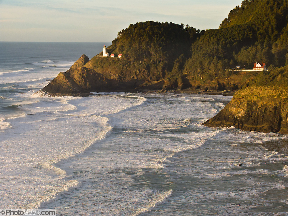 "Heceta Head Lighthouse at sunset in winter, seen from ""Lighthouse & Sealion Beach Vantage Point"" along Highway 101 on the Oregon coast, USA. Here, the Siuslaw Indians traditionally hunted sea lions and gathered sea bird eggs from offshore rocks. While seeking to extend Spanish hegemony in the late 1700s, Spanish explorer Bruno de Heceta mapped the mouth of the Columbia River and much more along the Pacific Northwest coast; and in 1862, the US Coast Survey named Heceta Head in his honor. Built atop a 56-foot tower in 1893, this Lightstation's coastal safety beacon was first illuminated in 1894. Perched 205 feet above the ocean, its fresnel lens focuses the brightest light on the Oregon coast, visible up to 21 miles out to sea. Heceta Head is found halfway between Yachats and Florence (2.1 miles south of Carl Washburne State Park). From the large parking lot, walk 1 mile round trip to the Lighthouse. (Heceta Head Lighthouse State Scenic Viewpoint was created in the 1990s by combining Heceta Head State Park with the former Devils Elbow State Park at the scenic cove at the mouth of Cape Creek.)"