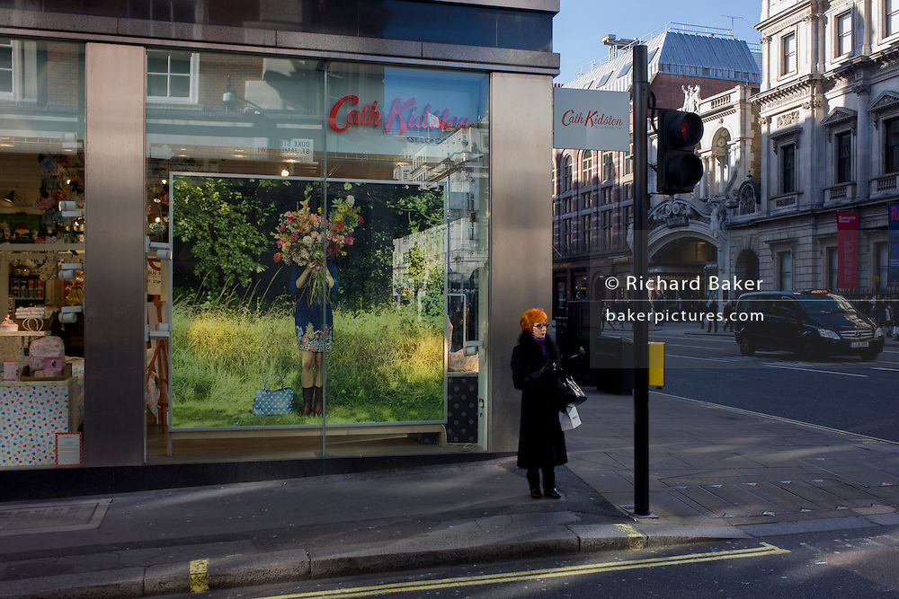 A lone auburn-haired woman waits to cross the road outside the Piccadilly branch of British fashion brand Cath Kidston on the corner of Duke Street, central London.