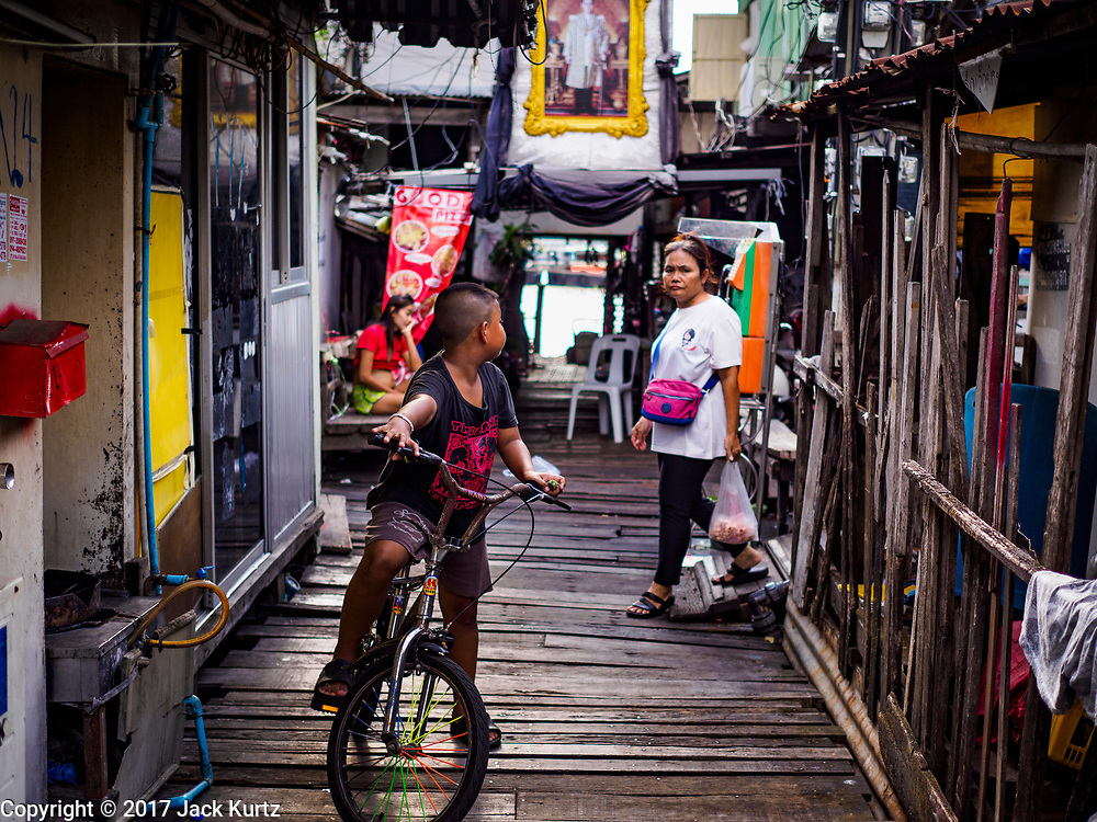 """20 JUNE 2017 - BANGKOK, THAILAND:  A boy on his bike waits for his mother in a community along the Chao Phraya River south of Krung Thon Bridge. This is one of the first parts of the riverbank that is scheduled to be redeveloped. The communities along the river don't know what's going to happen when the redevelopment starts. The Chao Phraya promenade is development project of parks, walkways and recreational areas on the Chao Phraya River between Pin Klao and Phra Nang Klao Bridges. The 14 kilometer long promenade will cost approximately 14 billion Baht (407 million US Dollars). The project involves the forced eviction of more than 200 communities of people who live along the river, a dozen riverfront  temples, several schools, and privately-owned piers on both sides of the Chao Phraya River. Construction is scheduled on the project is scheduled to start in early 2016. There has been very little public input on the planned redevelopment. The Thai government is also cracking down on homes built over the river, such homes are said to be in violation of the """"Navigation in Thai Waters Act."""" Owners face fines and the possibility that their homes will be torn down.              PHOTO BY JACK KURTZ"""