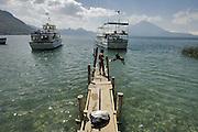 Scene around Lake Atitlan in Guatemala. Youngsters jump into the waters of Lake Atitlan in Santa Catarine Palopo, Guatemala.