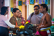 20 DECEMBER 2012 - KUALA LUMPUR, MALAYSIA:  People receive blessings from a Hindu priest at the Sri Mahamariamman Temple in Kuala Lumpur. The Sri Mahamariamman Temple is the oldest and richest Hindu temple in Kuala Lumpur, Malaysia. Founded in 1873, it is situated at edge of Chinatown in Jalan Bandar (formerly High Street). In 1968, a new structure was built, featuring the ornate 'Raja Gopuram' tower in the style of South Indian temples. From its inception, the temple provided an important place of worship for early Indian immigrants and is now an important cultural and national heritage in Malaysia.  PHOTO BY JACK KURTZ