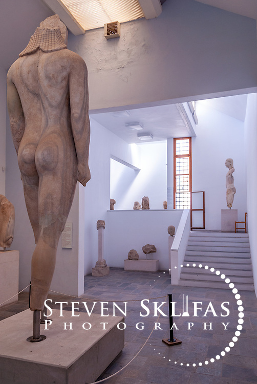 Greece. Samos. Rear view of the gigantic Kouros on display at the Archaeological Museum in Vathy or Samos town. Found in 1980 to the east of the Heraion, the colossal 4.80 metres high Kouros dates from 580 BC and was built from a single piece of grey veined Samian marble. According to the inscription on its left thigh, the Kouros is dedicated to Goddess Hera by a certain person named Isches. The Kouros is the largest free standing sculpture to have survived from the ancient Greek world