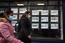 © Licensed to London News Pictures. 03/03/2021. London, UK. Members of the public wearing face masks walk past property advertisements in the window of an estate agents in Bayswater, west London. Chancellor Rishi Sunak will later deliver a  budget aimed at repairing damage to the UK economy caused by COVID-19. Photo credit: Ben Cawthra/LNP