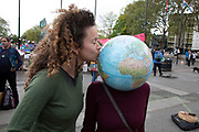 Climate change activists from the Extinction Rebellion group at the Marble Arch camp wears a globe of the Earth on her head as another protester kisses the planet in protest that the government is not doing enough to avoid catastrophic climate change and to demand the government take radical action to save the planet, on 24th April 2019 in London, England, United Kingdom. Extinction Rebellion is a climate change group started in 2018 and has gained a huge following of people committed to peaceful protests.
