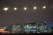 Night scene at London Bridge by the river Thames on a cold snowy winter evening. Snow in the lights by the river marks the sky like sparks.