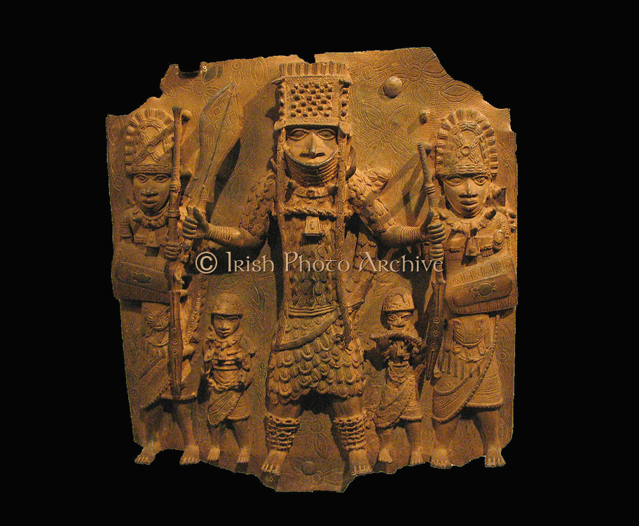 Plaque showing the facade of the royal palace.  Plaques may be seen attached to the pillars that support the palace roof.  They appear to have been made in matching pairs and are shown in such detail that some actual plaques can be readily identified.  Behind the main figures are two brass leopards and the stone axe heads that are kept on altars.  Attached to the roof of the tower is a large brass python.