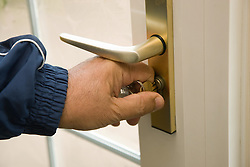 Close up of hand of older man locking a front door,