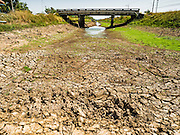 01 MARCH 2016 - CHACHOENGSAO, THAILAND:  An empty irrigation canal in Chachoengsao province of Thailand. Thai government officials have warned that there may not be enough water in the country's reservoirs to provide adequate water for farming, including fish and shrimp farms, industrial needs and domestic consumption. The government has told rice and fish farmers to reduce their use of water, and if necessary to reduce their crops. The current El Niño weather pattern is being blamed for the drought. The 2015 rainy season was well below normal and the 2016 rainy season could start two months late.   PHOTO BY JACK KURTZ