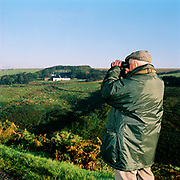 A foot follower of the Dulverton West Foxhounds watches the fox hunt at Warren Farm, Simonsbath, Exmoor, Somerset, UK through a pair of binoculars. Fox hunting is an activity involving the tracking, chase and sometimes killing of a fox by trained foxhounds and a group of unarmed followers lead by a 'master of foxhounds' who follow the hounds on foot or on horseback. This controversial sport, was banned in England and Wales in November 2004.