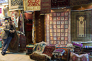 Salesman at Turkish carpet rug shop in The Grand Bazaar, Kapalicarsi, great market in Beyazi, Istanbul, Turkey