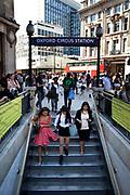 Three Asian girls descending the setps into Oxford Circus underground station. London.