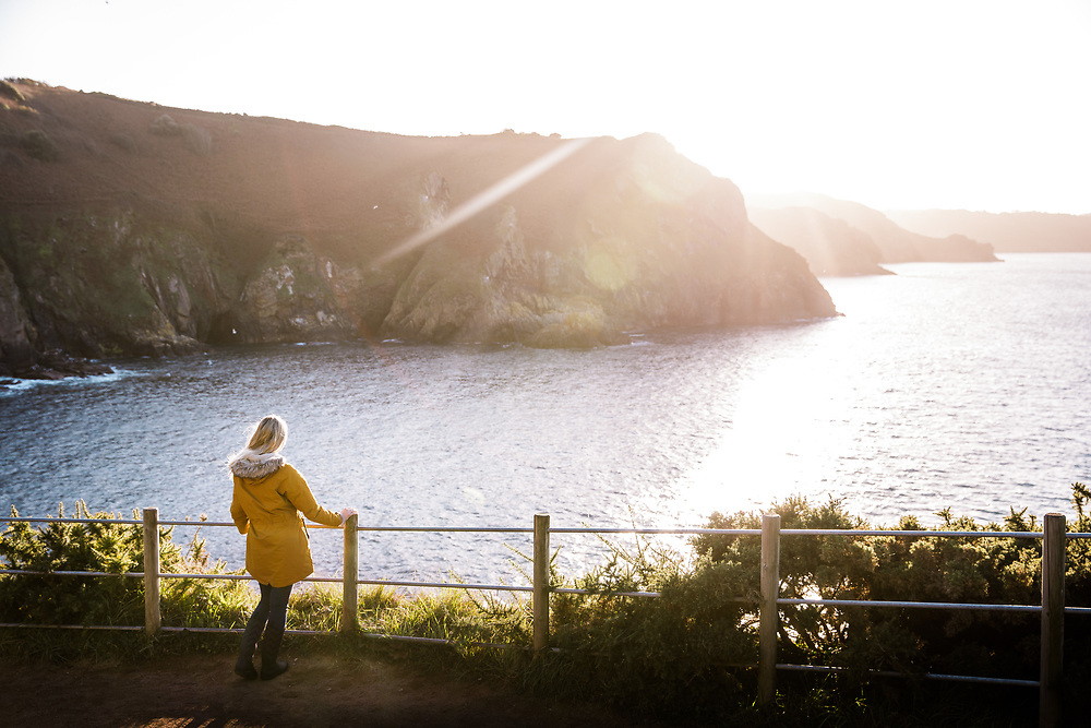 Woman enjoying the view of the sun setting over the sea and coastline from a cliff path near Devils Hole, a popular tourist attraction in Jersey, Channel Islands