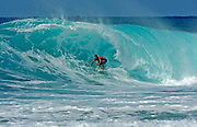A surfer rides a large wave at the Banzai Pipeline on the North Shore of Oahu, Hawaii, USA.