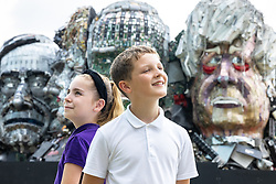 """© Licensed to London News Pictures. 21/07/2021. Stockport, UK.  St Matthews C of E Primary School students FRAYER OWEN (ten) and RILEY WAUDE (ten) are pictured in front of the sculpture . The E7 , a Mount Rushmore-style sculpture also known as """" Mount Recyclemore """" , is unveiled outside the Stockport headquarters of recommerce company musicMagpie , who commissioned the sculpture for the G7 summit in June to much media interest . The sculpture was created out of e-waste in the likeness of the G7 leaders by artist and founder of the Mutoid Waste Company, Joe Rush , and will serve as an educational attraction during events hosted this summer , in collaboration with Totally Stockport and Stockport Council . Photo credit: Joel Goodman/LNP"""