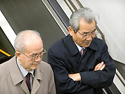 two businessmen standing on an escalator