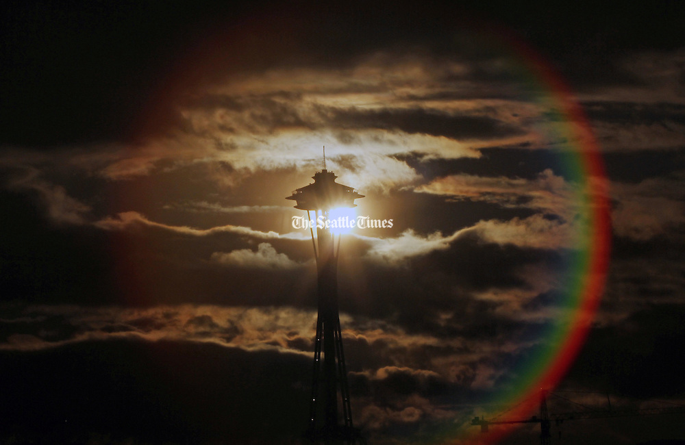 As the sun broke out in the west behind the Space Needle with rain in front of it, a rainbow formed north of the city.  (Alan Berner / The Seattle Times)