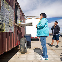 021913       Brian Leddy<br /> Mychelle Brown waits for her food at the Crownpoint Flea Market Tuesday during lunch. Members of the community are trying to bring about economic development and one of the first things they would like to do is find a better site for the flea market.