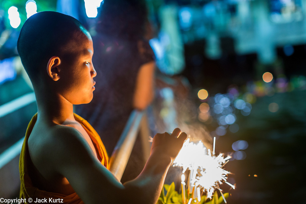 """17 NOVEMBER 2013 - BANGKOK, THAILAND:  A Buddhist novice lights sparklers on a Krathong he was floating in the Chao Phraya River near Wat Yannawa. Loy Krathong (also written as Loi Krathong) is celebrated annually throughout Thailand and certain parts of Laos and Burma (in Shan State). The name could be translated """"Floating Crown"""" or """"Floating Decoration"""" and comes from the tradition of making buoyant decorations which are then floated on a river. Loi Krathong takes place on the evening of the full moon of the 12th month in the traditional and they do this all evening on the 12th month Thai lunar calendar. In the western calendar this usually falls in November. The candle venerates the Buddha with light, while the krathong's floating symbolizes letting go of all one's hatred, anger, and defilements      PHOTO BY JACK KURTZ"""