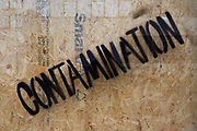 A detail of the word Contamination has been stencilled diagonally on a pane of glass in a building site in central London. The diagonally-printed words suggest the unsafe nature of whatever materials are behind the wooden screen of plyboard or chipboard.