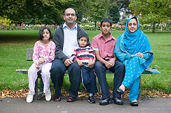 Young family sitting on a park bench together,
