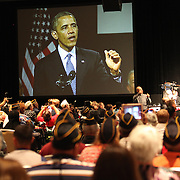 President Barack Obama is seen on the screen as he delivers remarks at the Disabled American Veterans  National Convention at the Orlando Hilton Ballroom in Orlando, Florida on Saturday, August 10, 2013. (AP Photo/Alex Menendez)