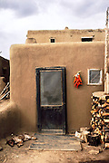 Taos Pueblo, New Mexico, USA. Back door of an adobe residence with a sleeping dog, firewood, and dried red chili peppers.