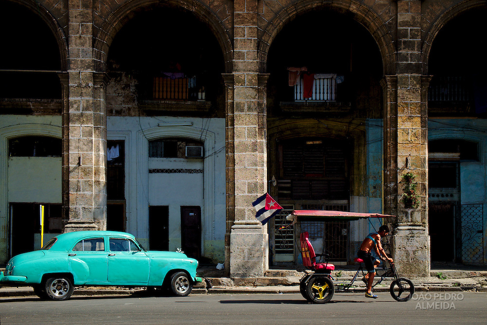 A classic American car parked outside the big arcades that are so typical of Centro Habana.