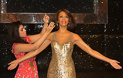 "© Licensed to London News Pictures. 21 October 2013. London, England. Pictured: hair sylist Caryn Bloom adds finishing touches. The 30-strong ""London Gospel Factory Choir"" today welcomed the wax figure of singer Whitney Houston at Madame Tussauds London, where it will be on display until the middle of December 2013. Photo credit: Bettina Strenske/LNP"