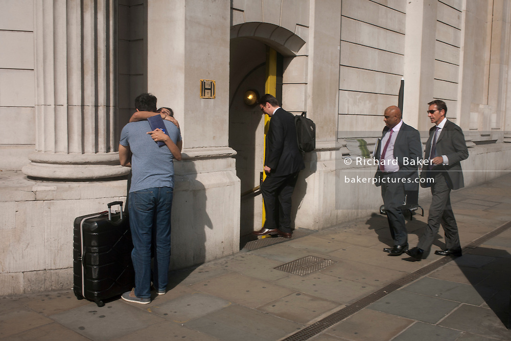A couple hug as Businessmen enter Bank Underground Station outside the Bank of England on 13th September 2016, in the City of London, England.