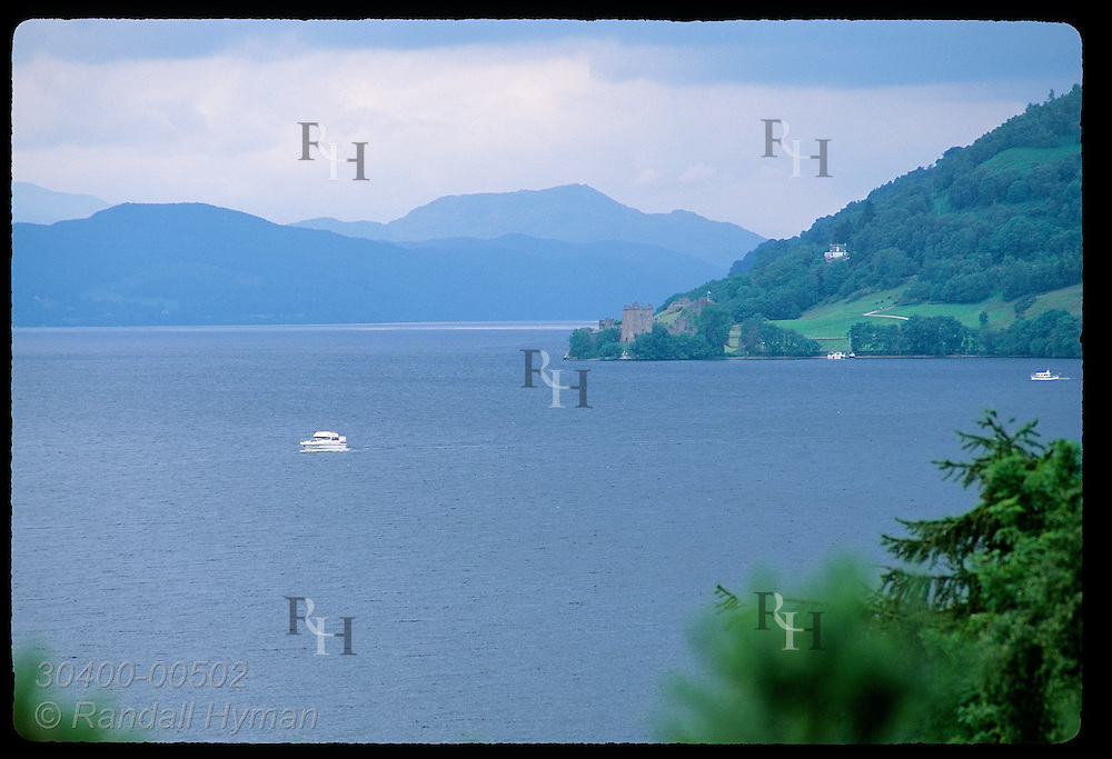 Motorboats ply the waters of Loch Ness near Urquhart Castle on a July morning; Drumnadrochit. Scotland