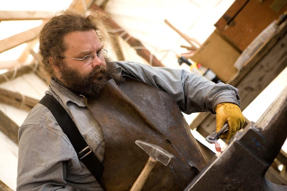 USA, Alaska,Blacksmith Jake Beimler works hot iron into art at his open air shop in downtown Ketchikan. MR