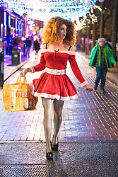 """© Licensed to London News Pictures . 23/12/2016 . Manchester , UK . A man , dressed as a woman , dressed as Santa Claus , walks along Canal Street . Revellers out in Manchester City Centre overnight during 2016's second """" Mad Friday """" , named for historically being one of the busiest nights of the year for the emergency services in the UK . Photo credit : Joel Goodman/LNP"""