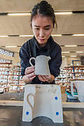 Student Bridgitte Chang getting a jug out of a mould - FACTORY: the seen and the unseen - an installation, in the form of a ceramics factory, by artist Clare Twomey. It is set up in the Blavatnik Building of the Tate Modern and launches the second year of Tate Exchange which, over 2017 and 2018, will focus on the theme of production.