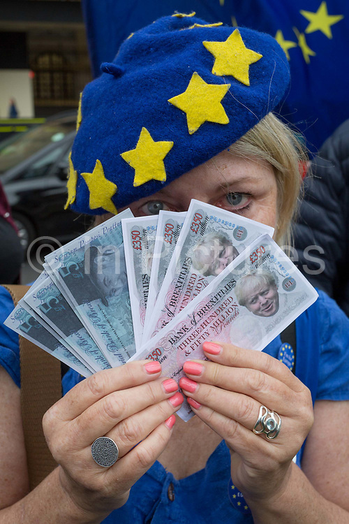 An anti-Brexit protestor outside the British Houses of Parliament in Westminster, shows home-printed bank notes with £350 million Pounds that Brexit campaigners promised to benefit the NHS, on 12th June 2018, in London, England.