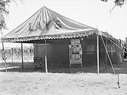 """5581 Lay's Motion picture theatre tent at the hop yard at the E. Clemens Horst hop ranch near Independence, Oregon. September 1, 1942. Advertising broadsides for upcoming films include two Castle war newsreels. These were only produced in 16mm, meaning that this theater was using 16 mm projectors. The front canopy is probably 24 feet wide, the main tent seating area is probably 32x32 with a 16' setback behind it for the screen. This size could easily be handled with a conventional bulb projector, rather than carbon arc. Probably a Bell & Howell Filmosound or something like it. They are advertising a Vaudeville stage show for this evening, with a magic show and a """"self supporting baby""""."""
