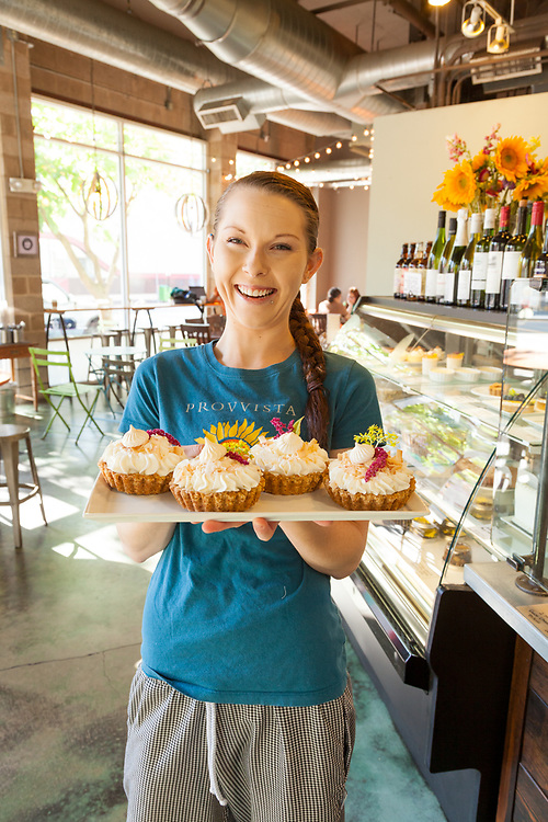 Baker with selection of sweet tarts at Noisette Pastry Kitchen in Eugene, Oregon